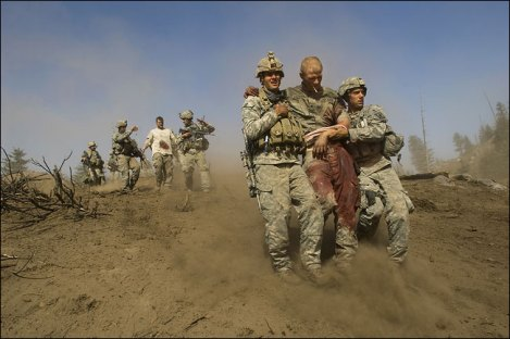 Afghanistan: injured soldier being helped by two comarades